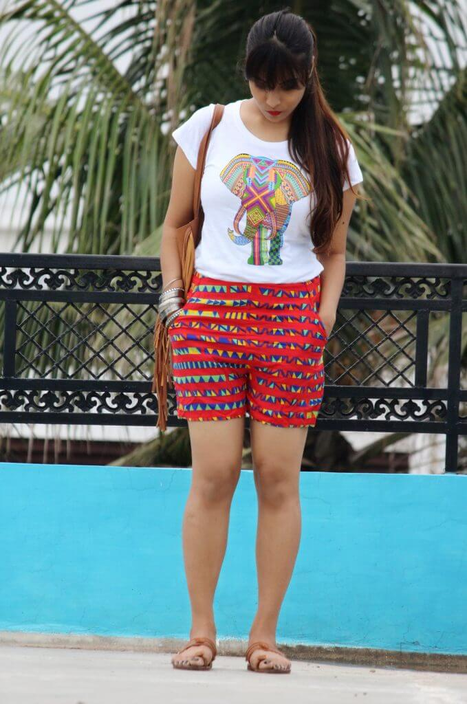Shrizan Wearing White Elephant Tee and Printed Red Shorts Looking Down Blue wall and Tree In Background
