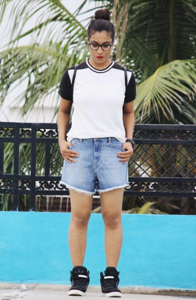 Shrizan In White TEE And Denim Shorts Looking Down Wearing Specs