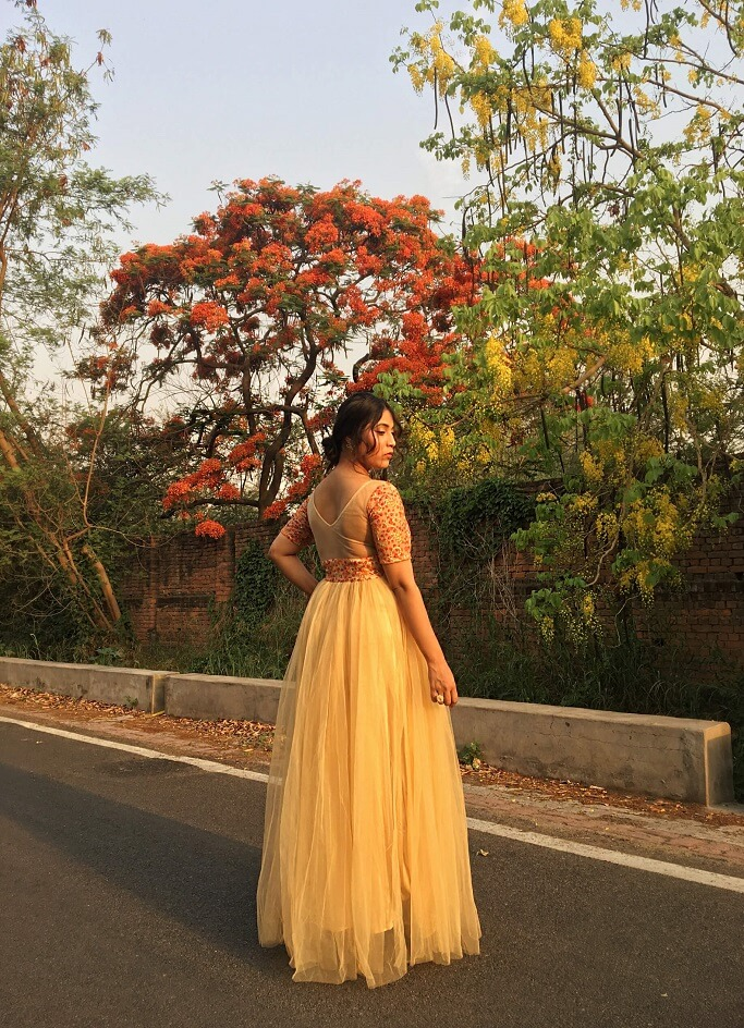 Shrizan  Wearing Golden Gown SIde Pose Trees In Back